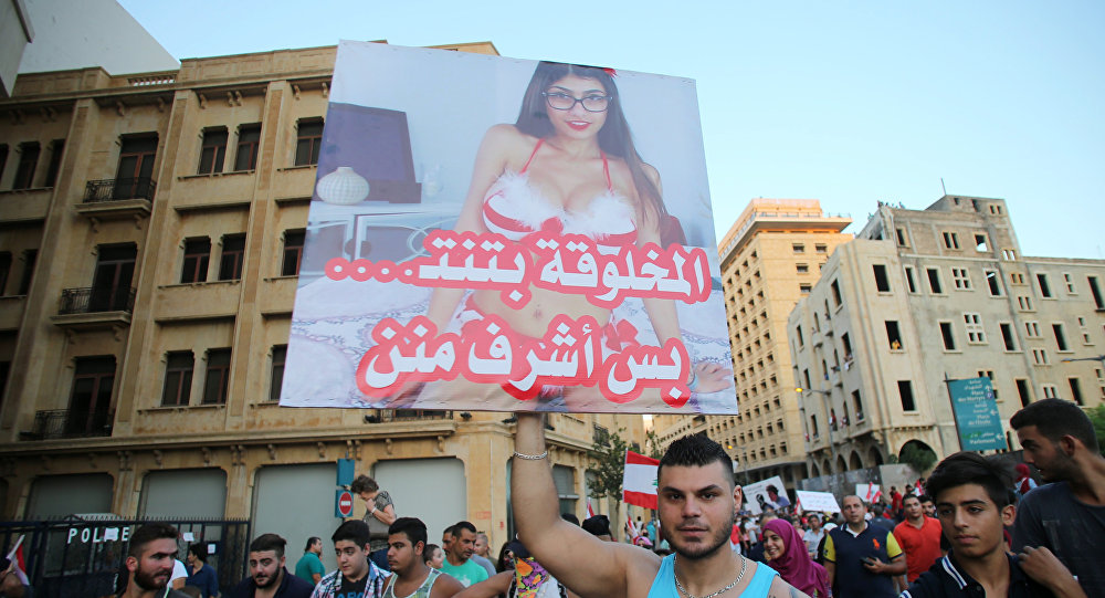 A Lebanese protester raises a poster bearing an image of Lebanese origin Porn Star Mia Khalifa and reading It is true that this woman does sex but she is more decent then them during a mass rally against a political class seen as corrupt and incapable of providing basic services on August 29, 2015 at the iconic Martyrs Square in Beirut