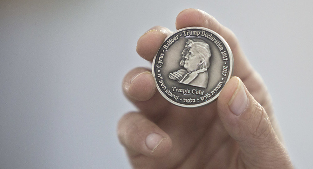 Head of the Mikdash Educational Center, Rabbi Mordecahi Persoss, holds a coin they minted bearing President Donald Trump's image to honor his recognition of Jerusalem as Israel's capital, in Tel Aviv, Israel, Wednesday, Feb. 28, 2018.