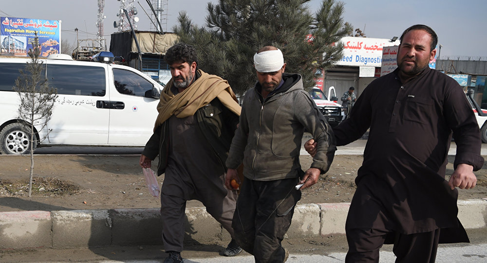 An Afghan resident assists an injured man near the site of a suicide car bomb attack targeting foreign troops in Kabul.