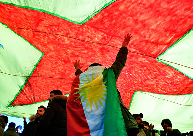 A demonstrator dressed in a Kurdistan flag cheers under a giant flag during a demonstration of Kurdish groups to protest against Turkey's offensive against Kurds in Syria's Afrin region, on March 3, 2018 in Berlin