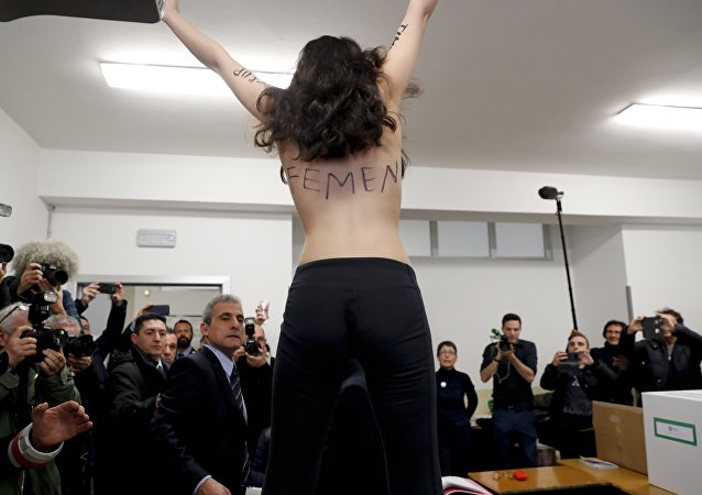 A topless Femen activist protests at a polling station where Italian former premier and leader of Forza Italia (Go Italy) party Silvio Berlusconi was about to vote, in Milan, Italy, Sunday, March 4, 2018.