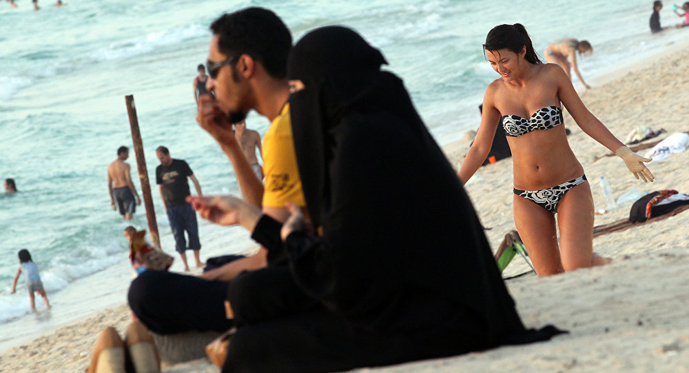 A foreign woman sunbathes near an Emirati couple on a beach in Dubai (File)