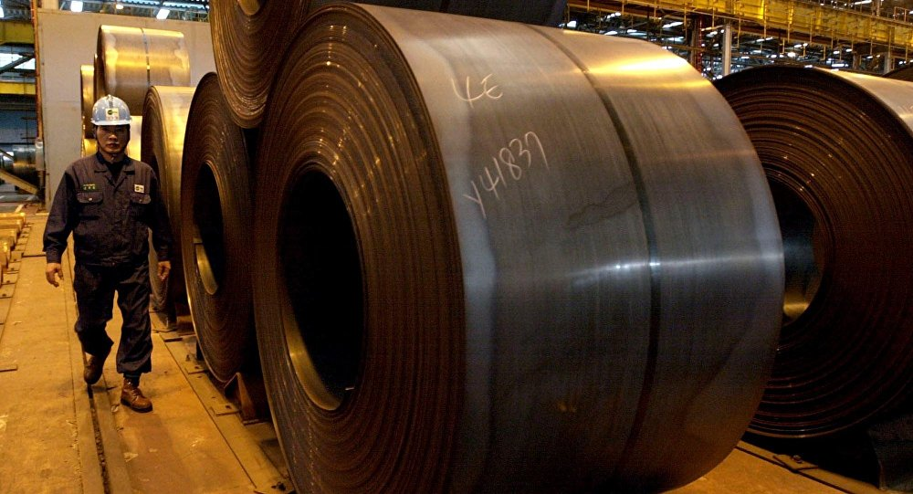 A worker walks by rolls of steel products at Posco steel mill in Pohang, south of Seoul, South Korea, Friday, Dec. 5, 2003