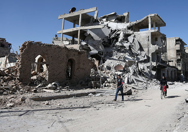 Syrians walk past destroyed buildings in the rebel-held town of Hamouria, in the besieged Eastern Ghouta region on the outskirts of the capital Damascus, on March 9, 2018