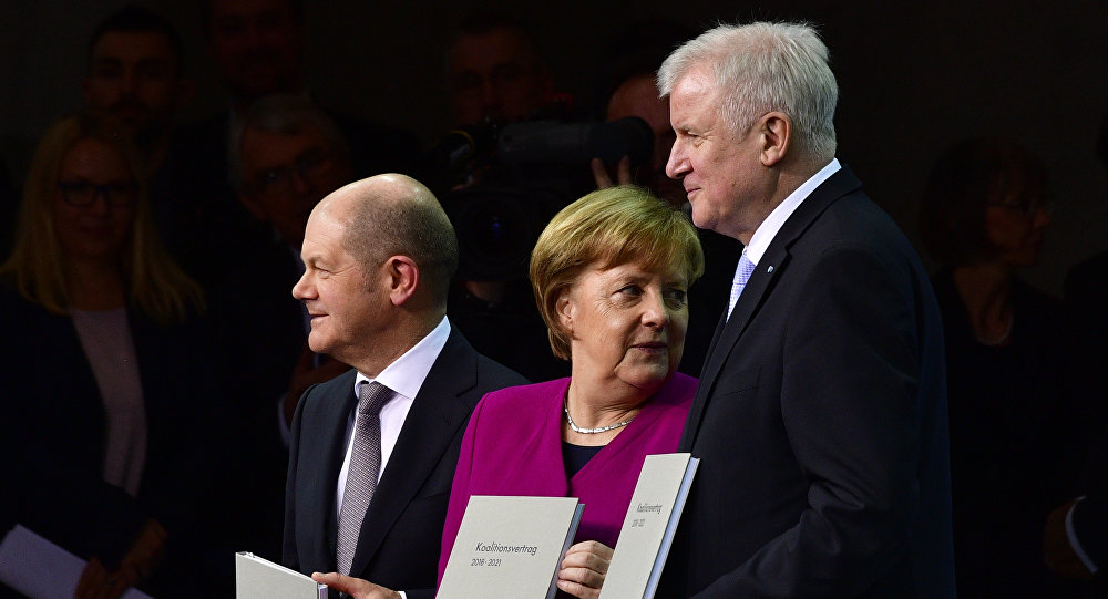 (L to R) Designated German Finance Minister and Vice-Chancellor Olaf Scholz of the SPD, German Chancellor Angela Merkel of the CDU and German Interior Minister Horst Seehofer of the CSU pose with the coalition treaty of the conservative CDU/CSU party and the Social Democrats to form a new government in Berlin, on March 12, 2018.