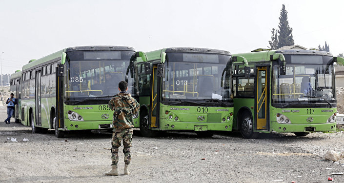 A picture taken on March 13, 2018 shows buses waiting to evacuate civilians on the government side of the Wafideen checkpoint on the outskirts of the Syrian capital Damascus neighbouring the Eastern Ghouta enclave