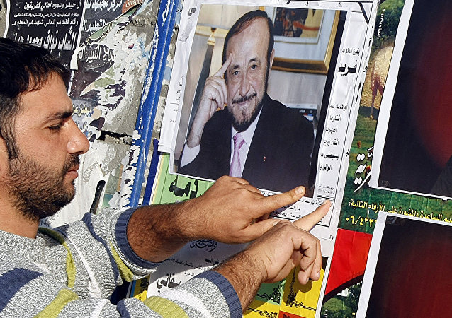 A member of the Alawite community pastes on a wall, in the northern Lebanese city of Tripoli 06 December 2007, pictures of Syrian opposition leader Rifaat al-Assad (R) and his son Ribal