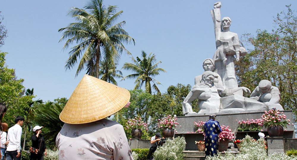 Visitors offer flowers at a war memorial dedicated to the victims of the My Lai massacre in the village of Son My during a ceremony marking the 50th anniversary of the massacre on March 16, 2018