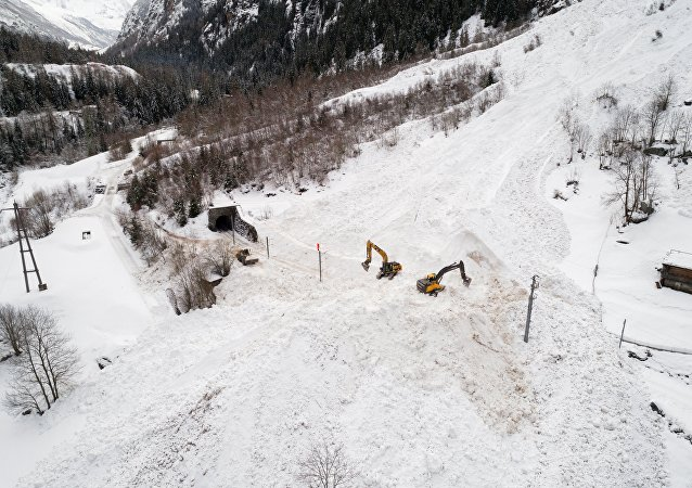 (File) Excavators remove the snow on the site of an avalanche that covered the railway of the Brig Visp Zermatt Bahn company between Visp and Taesch on January 10, 2018 near Sankt Niklaus, Swiss Alps