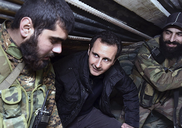 (File) This Wednesday, Dec. 31, 2014, file photo released by the Syrian official news agency SANA, Syrian President Bashar Assad, center, speaks with Syrian troops during his visit to the front line in the eastern Damascus district of Jobar, Syria