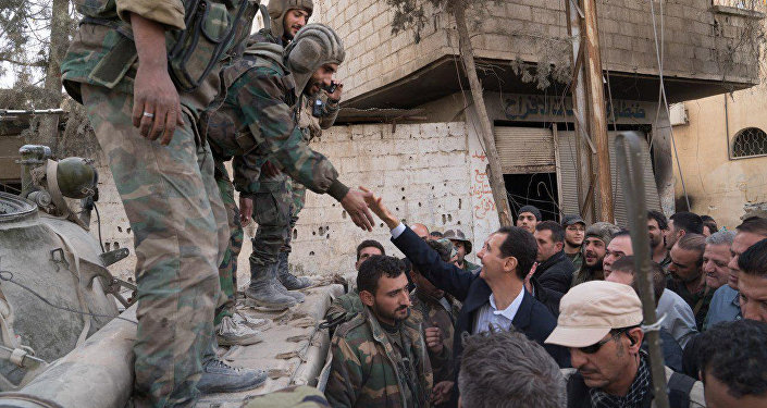 Syrian President Bashar al-Assad reaches out to shake the hand of a Syrian army soldier in eastern Ghouta, Syria, March 18, 2018