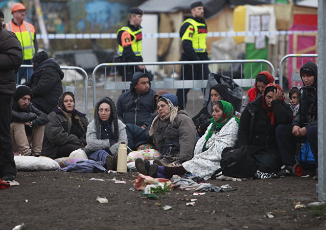 Migrants sit on the ground before leaving an illegal camp set up in Malmoe, on November 3, 2015, after the police started clearing the Roma camp after a months-long standoff between city authorities and about 200 people who had settled there without permissio
