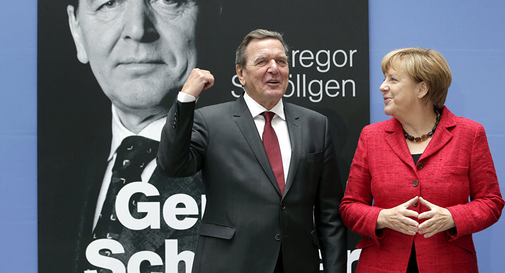 German Chancellor Angela Merkel, right, and former German Chancellor Gerhard Schroeder, left, pose during a photo call prior to the book presentation of Schroeder's biography in Berlin, Germany, Tuesday, Sept. 22, 2015