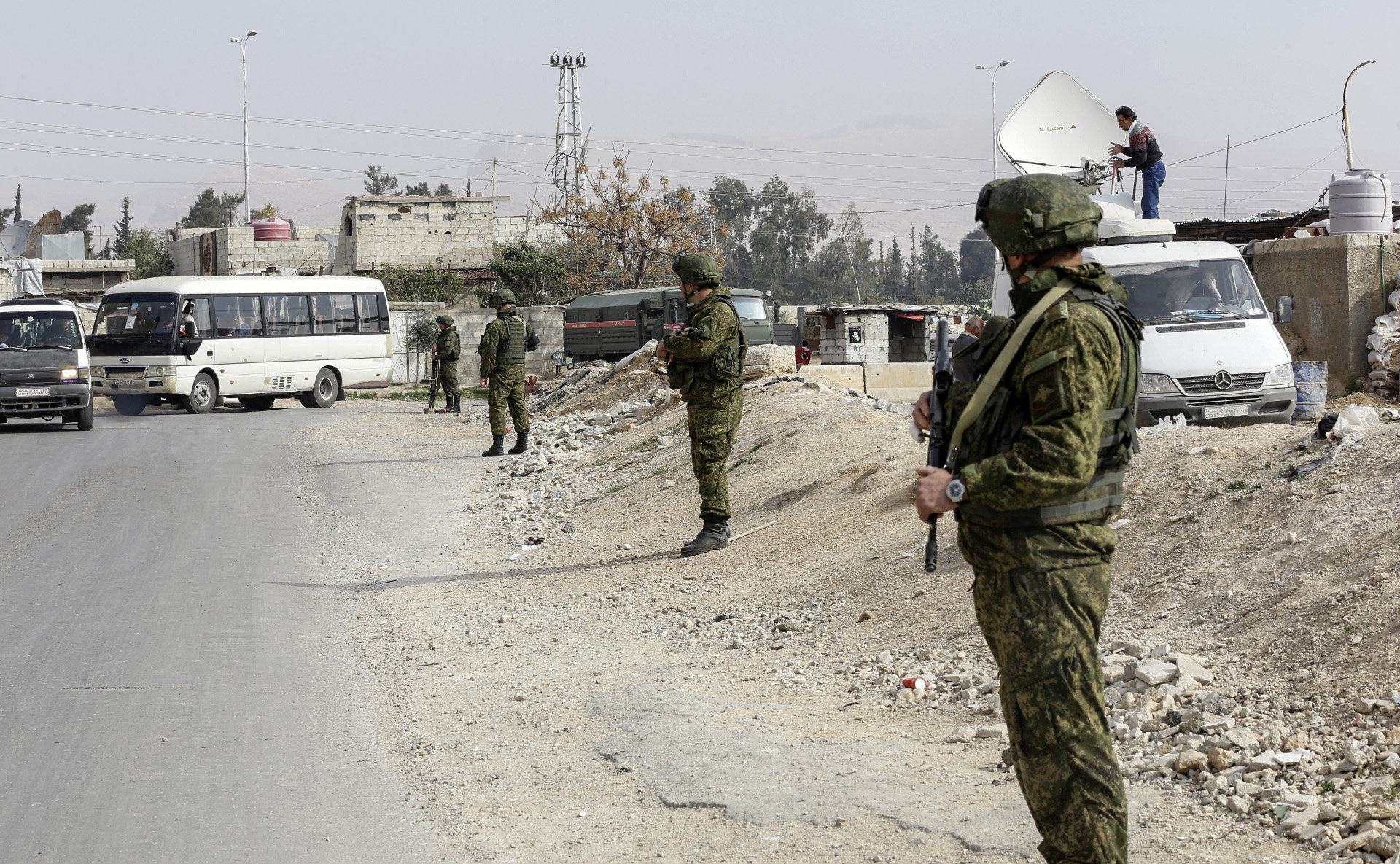 Russian military police members stand guard at the Wafideen checkpoint on the outskirts of the Syrian capital Damascus neighbouring the rebel-held Eastern Ghouta enclave on March 13, 2018, awaiting any civilians evacuating from the area