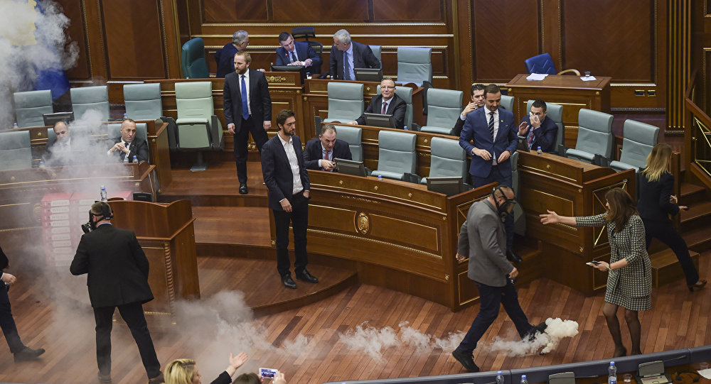 Kosovo policemen (R and L) prepare to remove a tear gas canister throwed by Kosovo's opposition lawmakers, in Pristina's parliament assembly room on March 21, 2018 before a vote on a key boarder deal with Montenegro
