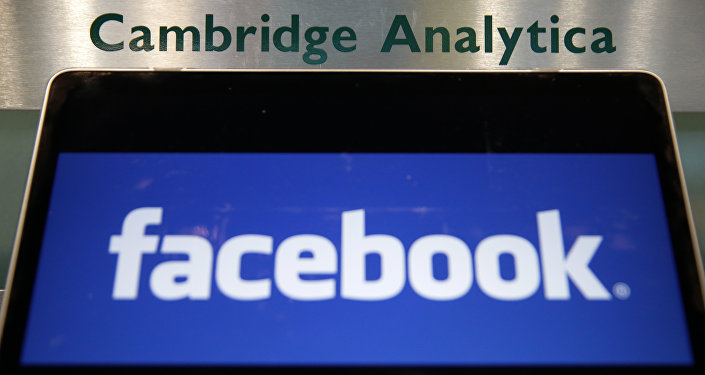 A laptop showing the Facebook logo is held alongside a Cambridge Analytica sign at the entrance to the building housing the offices of Cambridge Analytica, in central London