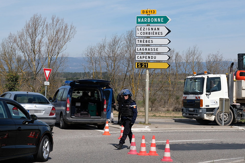 French gendarmes block the access to Trebes, where a man took hostages at a supermarket on March 23, 2018 in Trebes, southwest France