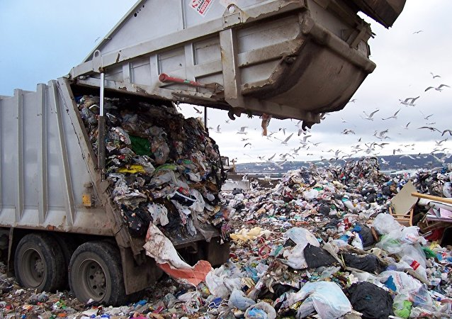 a garbage truck dumps trash in a US landfill