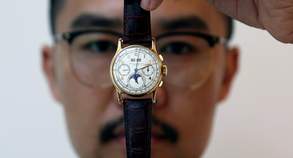 An exhibitor displays the Patek Philippe 18k gold perpetual chronograph wrist watch with moon phases belonging to the King Farouk, at the Christie's auction in Dubai, United Arab Emirates, March 19, 2018