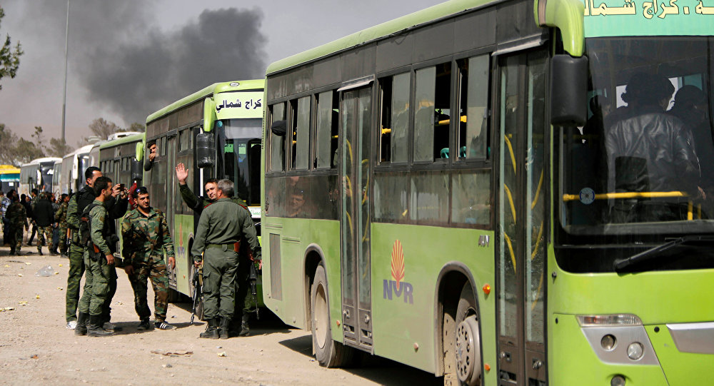 Members of Syrian forces of President Bashar al Assad stand next to buses carrying rebels and their families before they are evacuated, at Harasta highway outside Jobar, in Damascus, Syria March 25, 2018