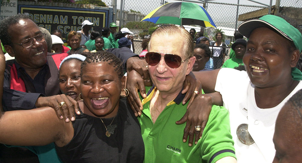 Edward Seaga (center, in sunglasses) is mobbed by supporters of the JLP in 2003