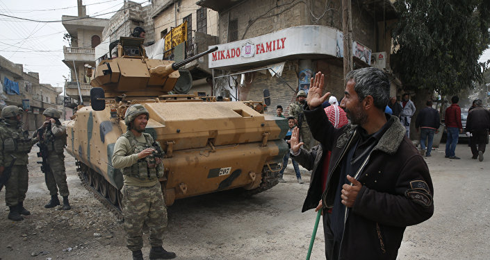 A Syrian man waves to Turkish soldiers securing the streets of the northwestern city of Afrin Syria during a Turkish government-organised media tour into northern Syria Saturday