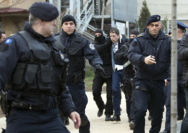 Kosovo police escort Marko Djuric a Serb official to a police station in Kosovo capital Pristina after he was arrested in northern Kosovo town of Mitrovica on Monday, March 26, 2018