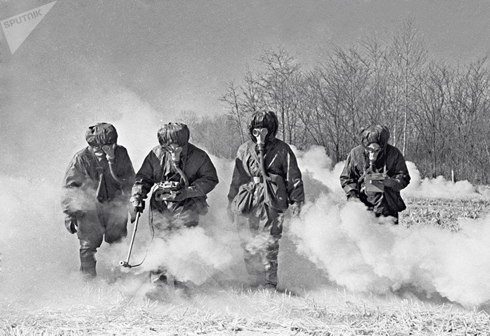 Soviet troops in special protective suits and gas masks conduct radiation reconnaissance. (File)