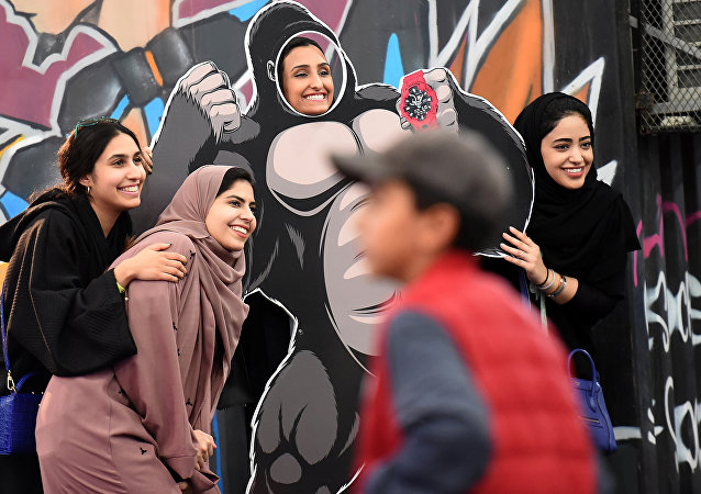 Saudi girls pose for a group picture as one stands behind a frame depicting King Kong, while attending the first ever Comic-Con Arabia event held in the capital Riyadh on November 25, 2017