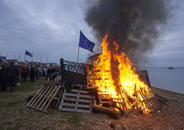The remains of a small boat flying European flags is burnt on a bonfire during a demonstration in Whitstable, southeast England on April 8, 2018 against the Brexit transition deal that would see Britain continue to adhere to the Common Fisheries Policy after formally leaving the EU