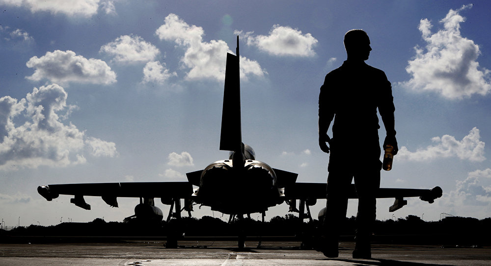 In this Thursday, Sept. 22, 2016 photo, a British soldier walks by a Typhoon aircraft before take off for a mission in Iraq, at RAF Akrotiri, near the southern coastal city of Limassol, in Cyprus