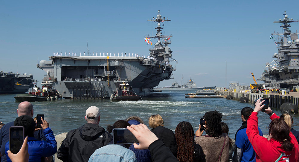 Family members look on as the U.S. Navy aircraft carrier USS Harry S. Truman departs with its carrier strike group towards the Middle East from Naval Station Norfolk, Virginia, U.S. April 11, 2018