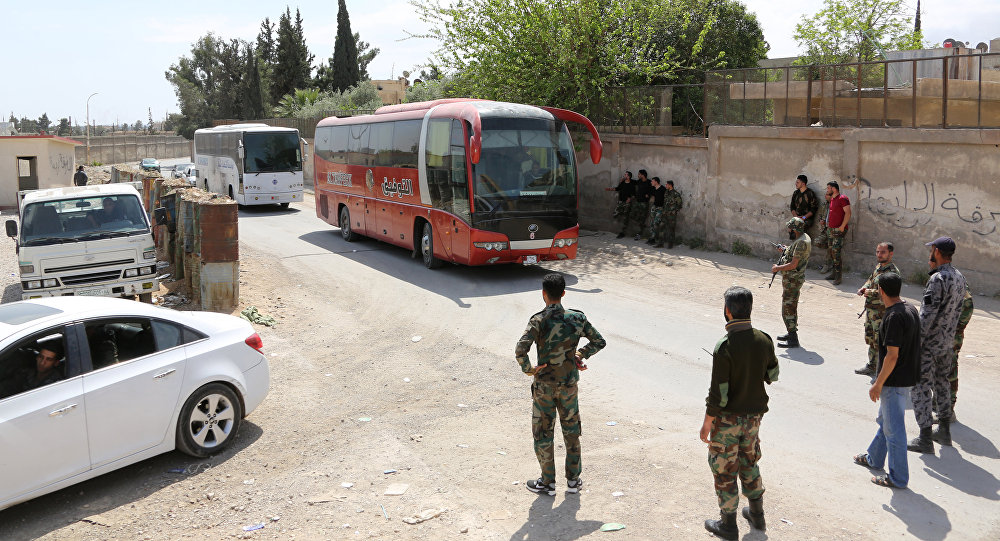 Pro-Syrian government forces gather around busses carrying Jaish al-Islam fighters and their families from their former rebel bastion of Douma as they arrive at the Syrian government-held side of the Wafideen checkpoint on the outskirts of Damascus, after being evacuated from the last rebel-held pocket in Estearn Ghouta on April 9, 2018
