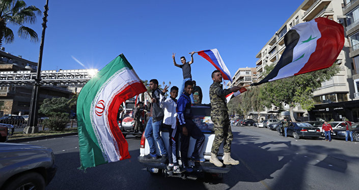 Syrian government supporters wave Syrian, Iranian and Russian flags as they chant slogans against U.S. President Trump during demonstrations following a wave of U.S., British and French military strikes to punish President Bashar Assad for suspected chemical attack against civilians, in Damascus, Syria, Saturday, April 14, 2018
