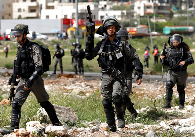 Israeli border police officers walk during clashes with Palestinians near the Jewish settlement of Beit El, near Ramallah, in the occupied West Bank April 13, 2018