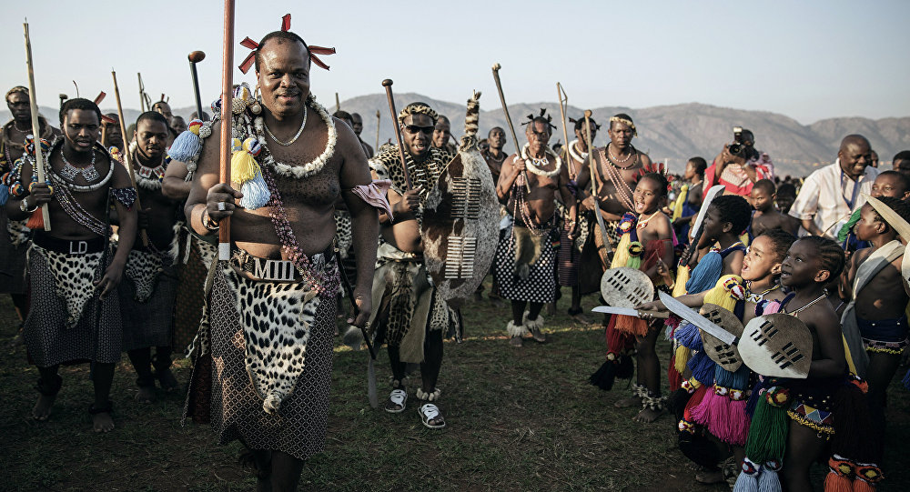 King Mswati III of Swaziland (L) walks in a traditional show of appreciation for maidens as they sing and dance on the last day of the annual royal Reed Dance at the Ludzidzini Royal palace on August 31, 2015 in Lobamba, Swaziland