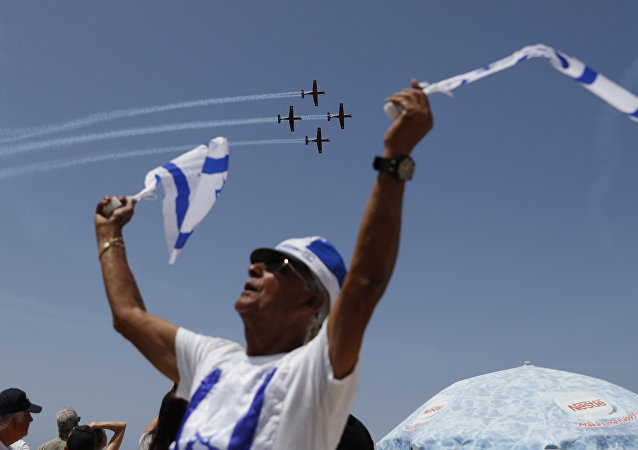 Israelis watch an air show during the festivities of the 70th Independence Day, on April 19, 2018 in the Mediterranean coastal city of Tel Aviv.