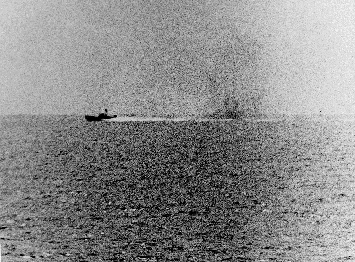 Photograph taken from the U.S. Navy destroyer USS Maddox (DD-731) during her engagement with three North Vietnamese motor torpedo boats in the Gulf of Tonkin, 2 August 1964. The view shows one of the boats racing by, with what appears to be smoke from Maddox' shells in its wake.