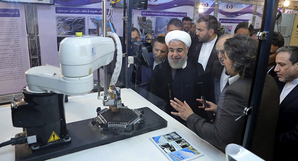 In this photo released by an official website of the office of the Iranian Presidency, President Hassan Rouhani listens to explanations on new nuclear achievements at a ceremony to mark National Nuclear Day, in Tehran, Iran, April 9, 2018