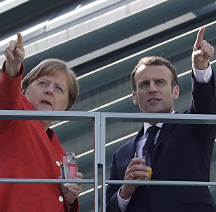 French President Emmanuel Macron, right, and German Chancellor Angela Merkel take a break on a balcony of Merkel's office after a meeting in the chancellery in Berlin, Germany, Thursday, April 19, 2018