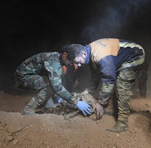 Syrian security forces members remove human remains at the site were discovered two mass graves believed to contain the bodies of civilians and troops killed by the Islamic State militants, in the village of Wawi near the northern city of Raqqa, Syria (File)
