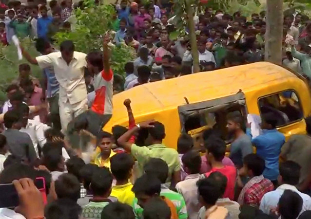 People gather around a school bus after it collided with a train in Uttar Pradesh, India April 26, 2018, in this screen grab taken from video