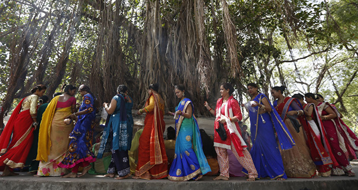 (File) Indian Hindu married women tie cotton threads around a Banyan tree as they perform rituals on the first day of Vat Savitri festival in Ahmadabad, India, Tuesday, June 6, 2017