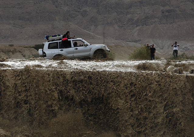 A car drives through flooded water running through a valley blocking the main road along the Dead Sea in the Judean desert, near the desert fortress of Masada north of Ein Bokek, following heavy rainfall in the mountains on April 25, 2018