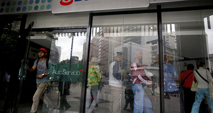 A customer leaves a Banesco's bank branch as other wait in line, in Caracas, Venezuela, Friday, May 4, 2018
