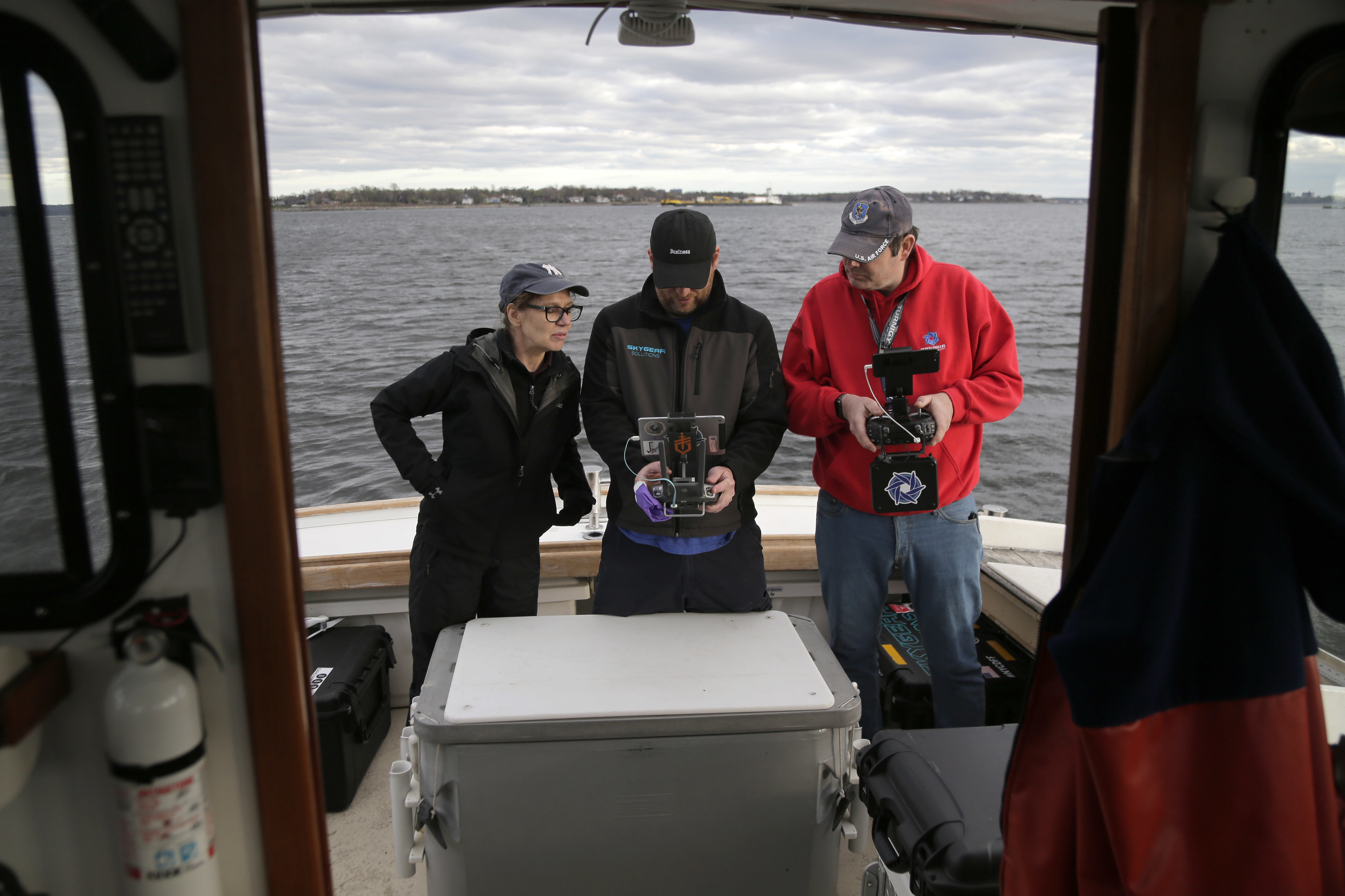 In this April 29, 2018, photo, artist Melinda Hunt, president of The Hart Island Project, left, and drone operator Parker Gyokeres, right, look over the footage recorded by Daniel Herbert from the drone flight over Hart Island in New York