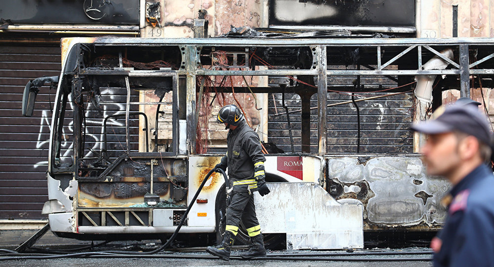 A firefighter walks next to a burned bus in downtown Rome, Italy May 8, 2018