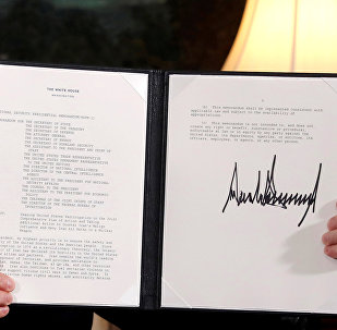 U.S. President Donald Trump holds up a proclamation declaring his intention to withdraw from the JCPOA Iran nuclear agreement after signing it in the Diplomatic Room at the White House in Washington, U.S. May 8, 2018