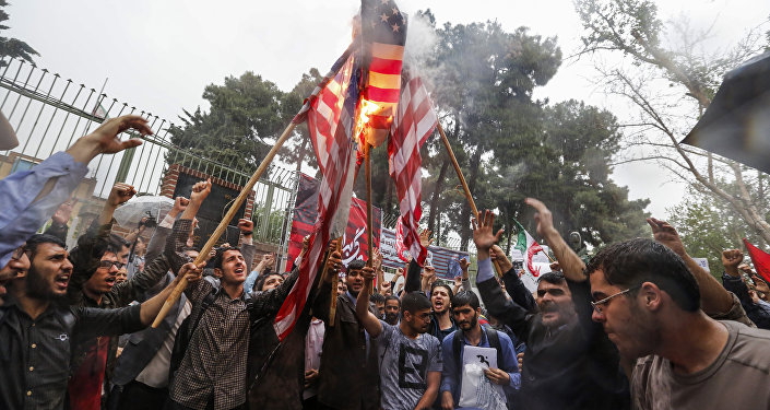 Iranians burn US flags during an anti-US demonstration outside the former US embassy headquarters in the capital Tehran on May 9, 2018