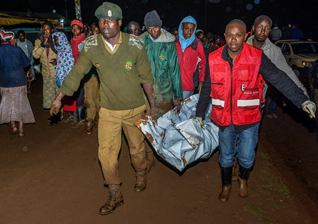 People carry a victim's body from a residential area after Patel dam burst its bank at Solai, about 40 kilometres north of Nakuru, Kenya, on May 10, 2018